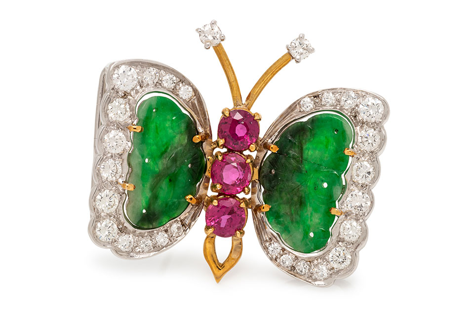Diamond, Jade and Butterfly Brooch. Containing 28 round brilliant cut diamonds weighing approximately 1.50 carats total, two carved ruby plaques and three round mixed cut rubies measuring approximately 4.60 mm in diameter. Mounted in bicolor gold. 6.15 dwt. Estimate: $500-700. Price realized: $3,289.