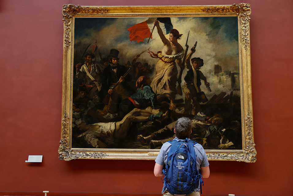 "A picture taken on June 23, 2020 shows a man pictured during a press visit, in front of the French Romantic artist Eugene Delacroix' painting the ""Liberty Leading the People"", at the Louvre in Paris. The Louvre museum will reopen its doors on July 6, 2020, after months of closure due to lockdown measures linked to the COVID-19 pandemic, caused by the novel coronavirus. The coronavirus crisis has already caused ""more than 40 million euros in losses"" at the Louvre, announced its president and director Jean-Luc Martinez, who advocates a revival through ""cultural democratization"" and is preparing a ""transformation plan"" for the upcoming Olympic Games in 2024. THOMAS SAMSON / AFP."