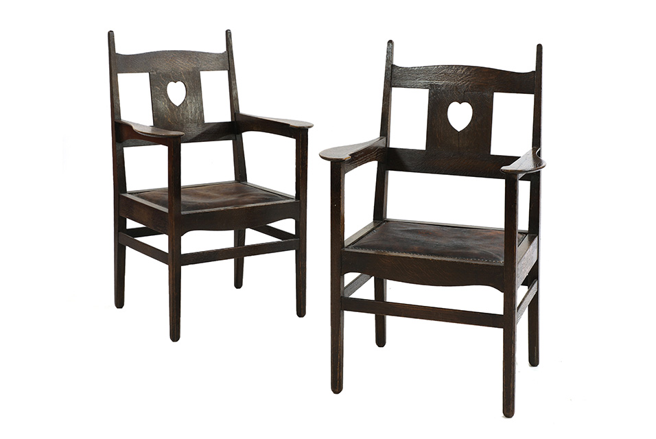 C.F.A Voysey (1857-1941), a pair of oak armchairs, c.1902, with leather and studded drop in seats, 62.5cm wide, 54.5cm deep. 100.5cm high, seat 42.5cm (2). Estimate: £20,000-30,000.