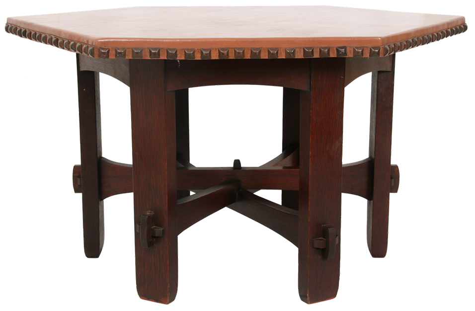 A Gustav Stickley No. 410-L table ($12/15,000) has a hexagonal top over an arched apron, circa 1900, with the base in original finish, 30½ inches tall, diameter is 49 inches.
