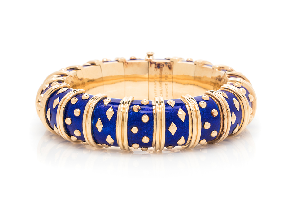 Tiffany & Co., Schlumberger, Yellow Gold and Enamel 'Dot Losange' Bangle Bracelet. Consisting of a semi-flexible bangle bracelet with blue paillonnè enamel and studded with yellow gold accents. Estimate: $15,000 - $20,000.