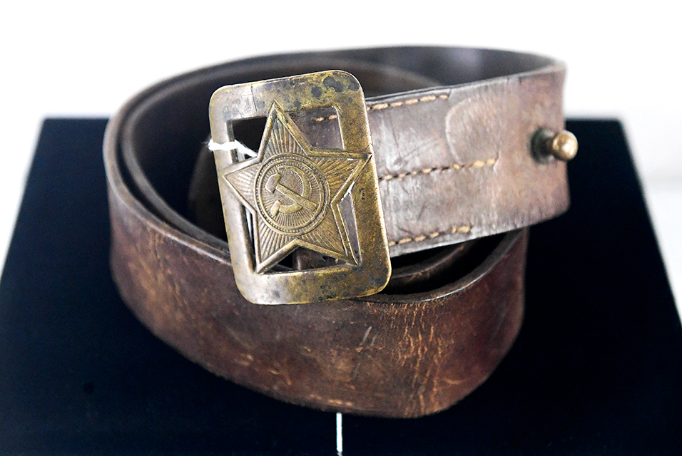 """A Soviet WW2 era Officers Belt and Buckle is displayed during an auction preview for """"The Cold War Relics Auction - Featuring the KGB Espionage Museum Collection"""" at Julien's Auctions in Beverly Hills, California on February 8, 2021. Measuring 45 1/2 inches, the belt and buckle are estimated at $100-200. Frederic J. BROWN / AFP.  by Laurent Banguet"""