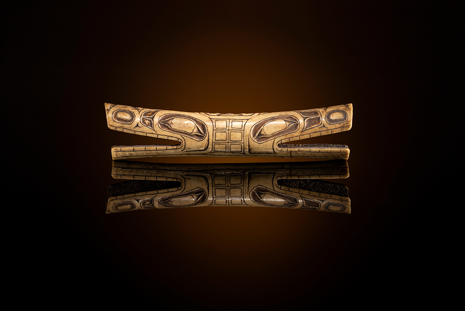 Tsimshian Carved Soul Catcher carved of bone; open-mouthed wolves are separated by a central human figure; remnants of red pigment; pierced through for attachment. Overall length 8.25 in. x diameter 2 in. Early 19th century. Estimate: $40,000 - $60,000.